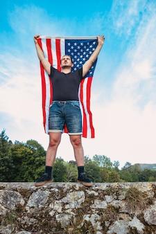 남자가 미국 미국 국기를 흔들고 있다. 애국심의 개념