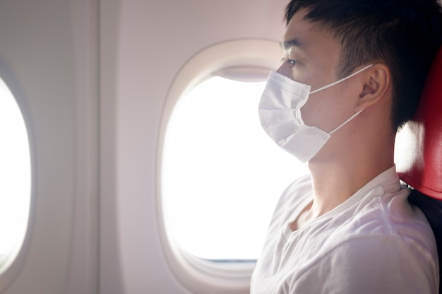 Man is wearing protective mask onboard in the aircraft, travel under covid-19 pandemic