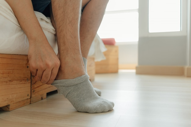Man is wearing socks into his feet in the bedroom.