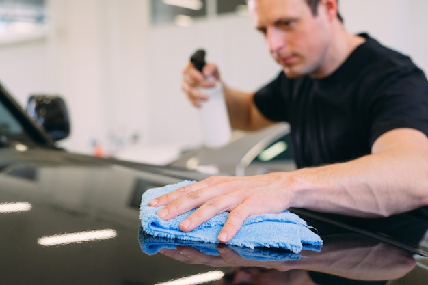 The man is wiping with a cloth body of a brilliant car.