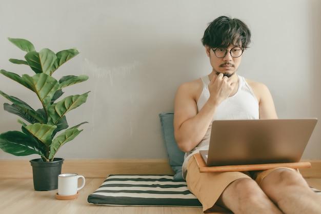 남자는 그의 아파트의 거실에서 일하고있다