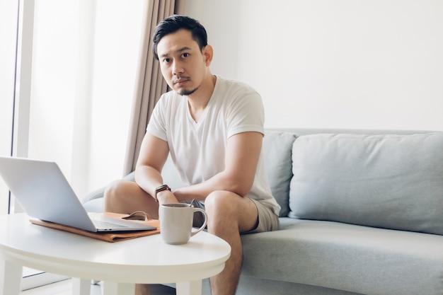Мужчина работает на своем ноутбуке в гостиной с чашкой кофе.