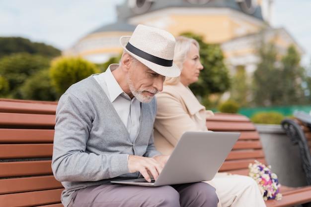 Человек работает на ноутбуке, женщина на него обижена.