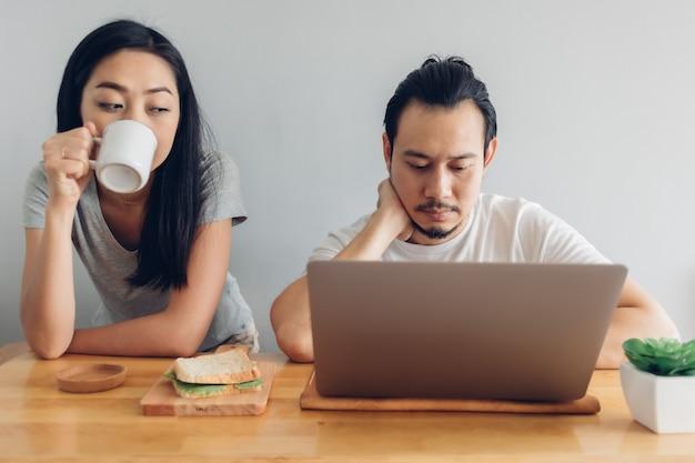 男性は妻のサポートでオンラインで作業しています