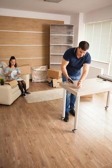 男性は新しい家で電動ドライバーを使用して家具の組み立てを行っています。ツールを使用している男性。