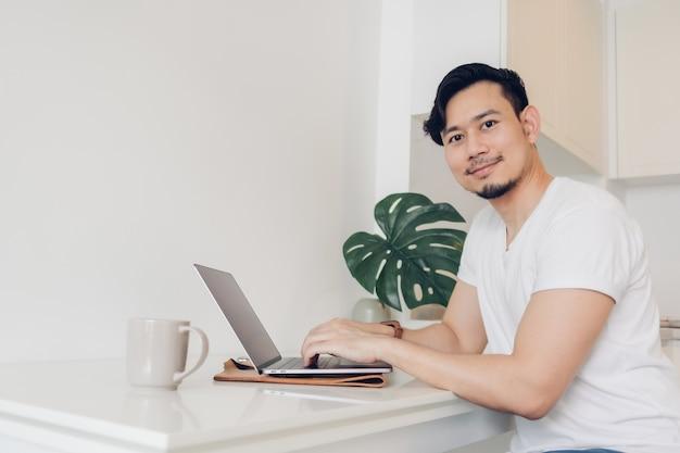 男は彼の白いワークスペーステーブルの上のラップトップで働いています。