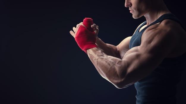 남자는 검은 배경에 격리된 빨간색 권투 랩으로 손을 감싸고 있습니다. 강한 손과 주먹, 훈련 및 활동적인 운동 준비