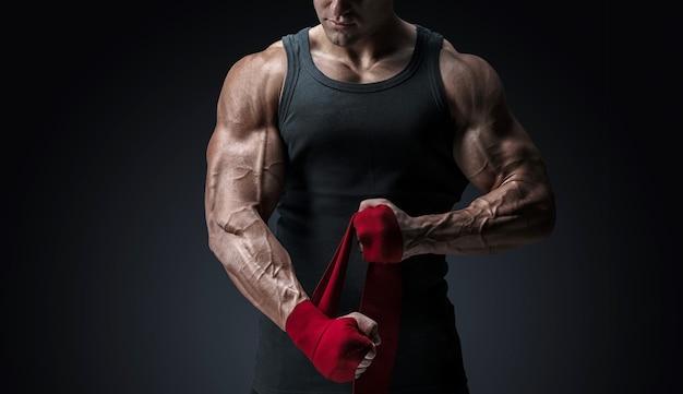 남자는 격리된 빨간색 권투 랩으로 손을 감싸고 있습니다. 강한 손과 주먹, 훈련 및 활동적인 운동을 위한 준비 검정색 배경에 자른