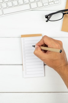 A man is writing on to do list paper