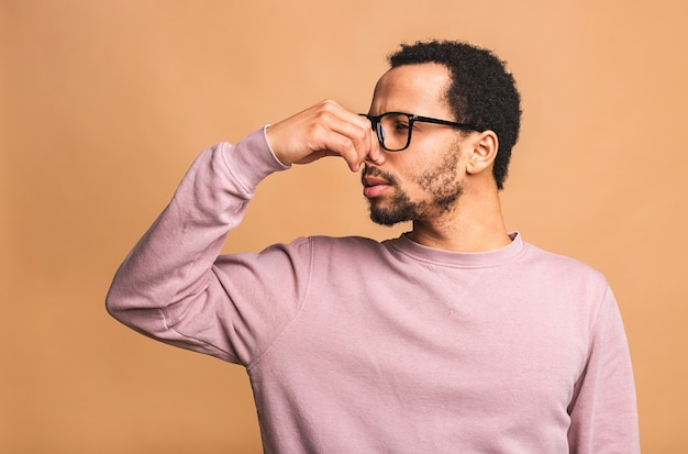 Man isolated against beige smelling something stinky and disgusting, intolerable smell, holding breath with fingers on nose