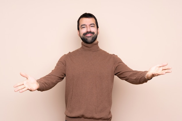 Man over isolated background presenting and inviting to come with hand