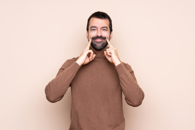 Man over isolated background smiling with a happy and pleasant expression