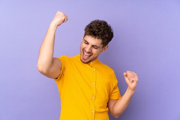 승리를 축 하하는 보라색 벽에 고립 된 남자