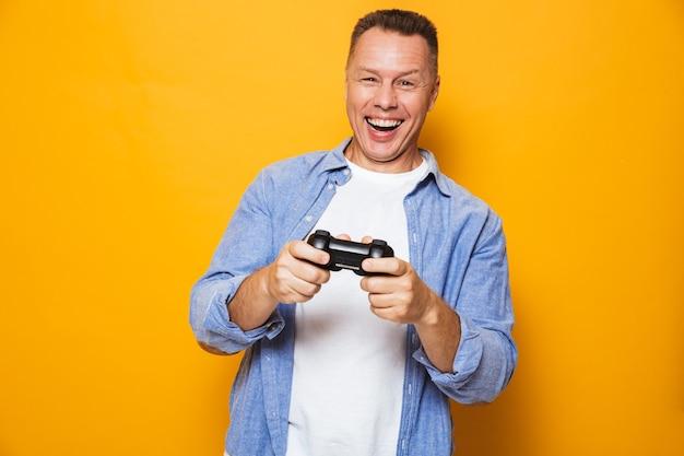 Человек, изолированные на желтой стене, играют в игры с джойстиком.