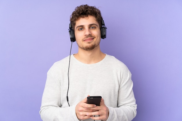 Man isolated on purple wall listening music with a mobile and looking front