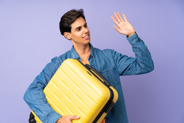 Man over isolated purple wall in vacation with travel suitcase and saluting