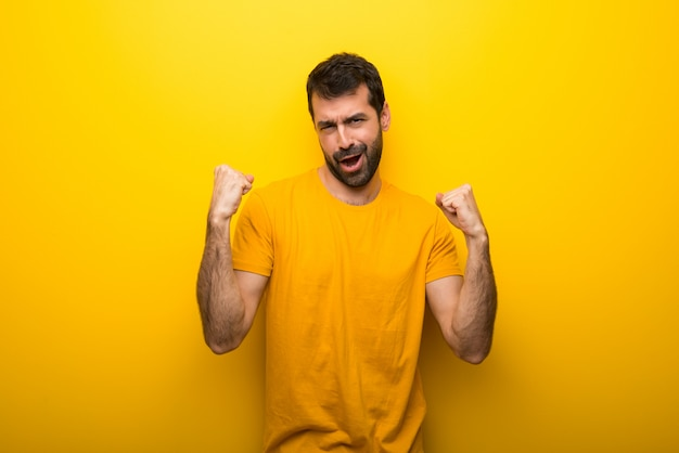 Man on isolated vibrant yellow color celebrating a victory