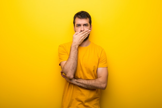 Man on isolated vibrant yellow color covering mouth with hands for saying something inappropriate