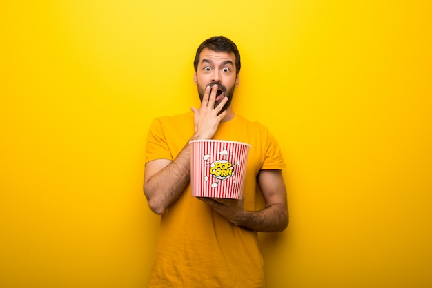 Man on isolated vibrant yellow color eating popcorns