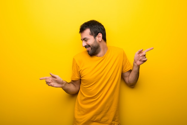 Man on isolated vibrant yellow color enjoy dancing while listening to music at a party