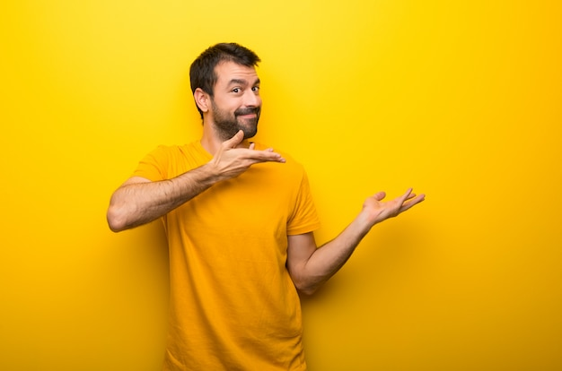 Man on isolated vibrant yellow color extending hands to the side for inviting to come