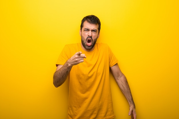Man on isolated vibrant yellow color frustrated by a bad situation and pointing to the front