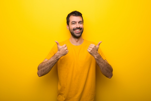 Man on isolated vibrant yellow color giving a thumbs up gesture with both hands and smiling
