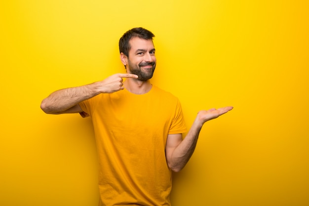 Man on isolated vibrant yellow color holding copyspace imaginary on the palm to insert an ad