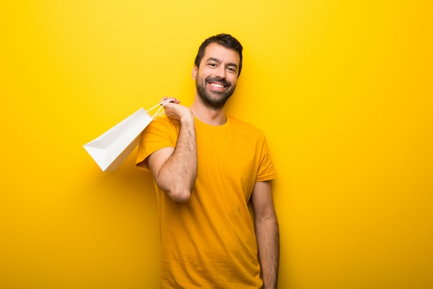 Man on isolated vibrant yellow color holding a lot of shopping bags