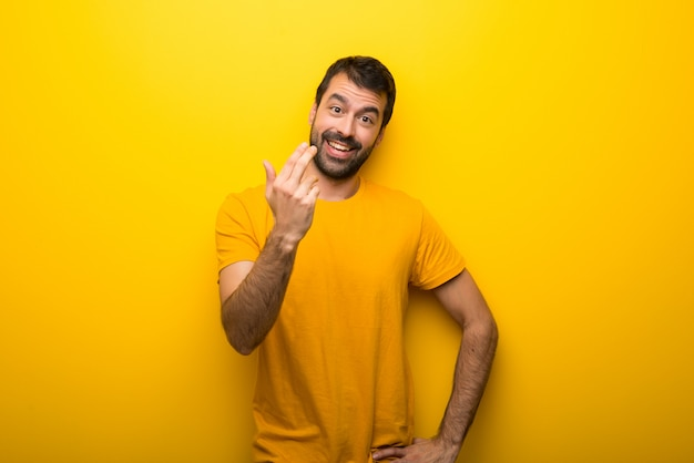 Man on isolated vibrant yellow color inviting to come with hand. happy that you came