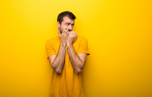 Man on isolated vibrant yellow color is a little bit nervous and scared putting hands to mouth