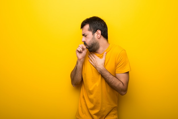 Man on isolated vibrant yellow color is suffering with cough and feeling bad