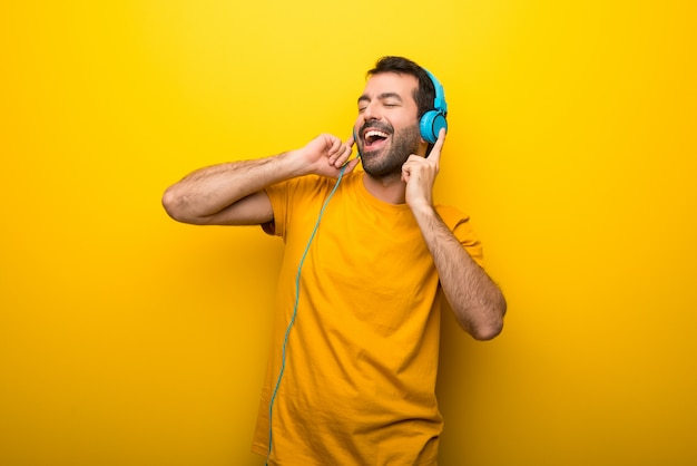 Man on isolated vibrant yellow color listening to music with headphones