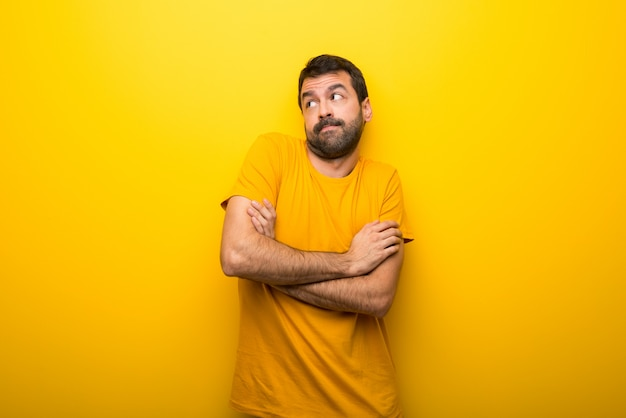 Man on isolated vibrant yellow color making doubts gesture while lifting the shoulders