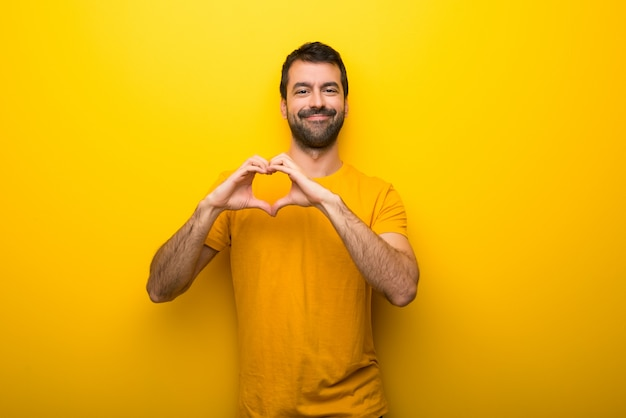 Man on isolated vibrant yellow color making heart symbol by hands