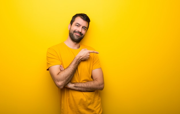 Man on isolated vibrant yellow color pointing finger to the side in lateral position