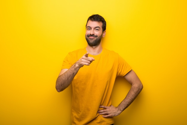 Man on isolated vibrant yellow color points finger at you with a confident expression