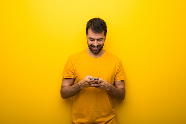 Man on isolated vibrant yellow color sending a message or email with the mobile