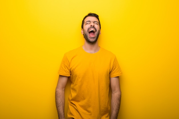 Man on isolated vibrant yellow color shouting to the front with mouth wide open