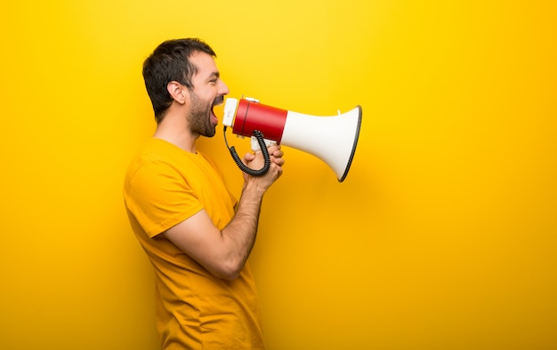 Man on isolated vibrant yellow color shouting through a megaphone to announce something in lateral position