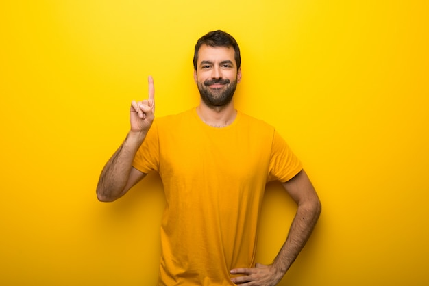 Man on isolated vibrant yellow color showing and lifting a finger in sign of the best