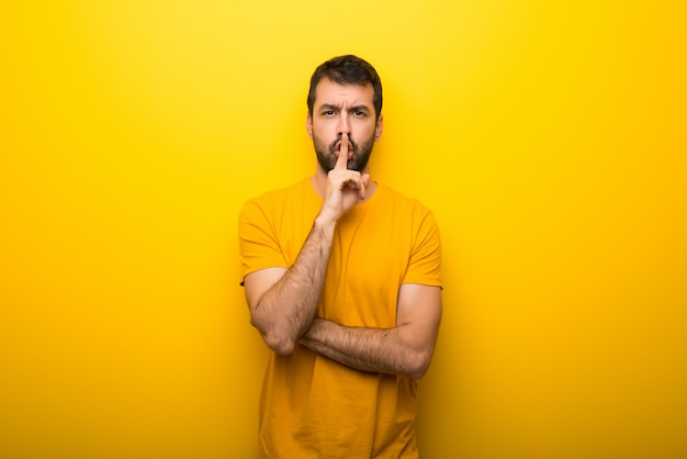 Man on isolated vibrant yellow color showing a sign of silence gesture putting finger in mouth
