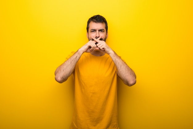 Man on isolated vibrant yellow color showing a sign of silence gesture