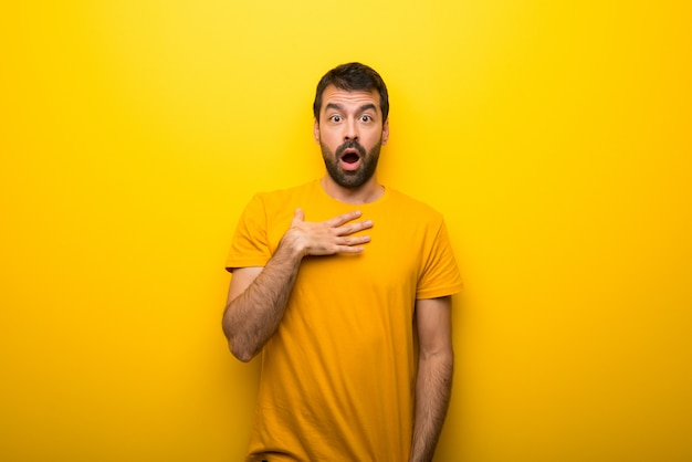 Man on isolated vibrant yellow color surprised and shocked while looking right