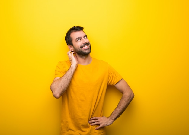Man on isolated vibrant yellow color thinking an idea while scratching head