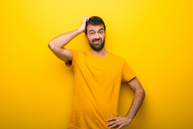 Man on isolated vibrant yellow color with an expression of frustration and not understanding