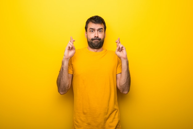 Man on isolated vibrant yellow color with fingers crossing and wishing the best