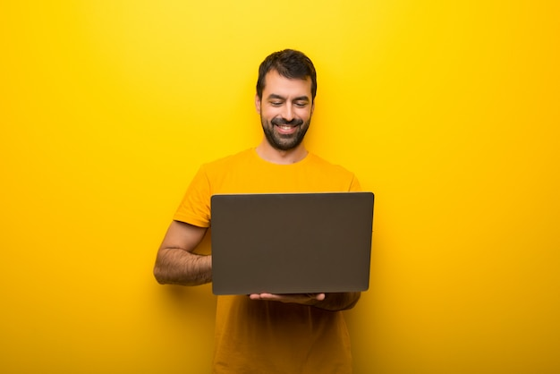 Man on isolated vibrant yellow color with laptop