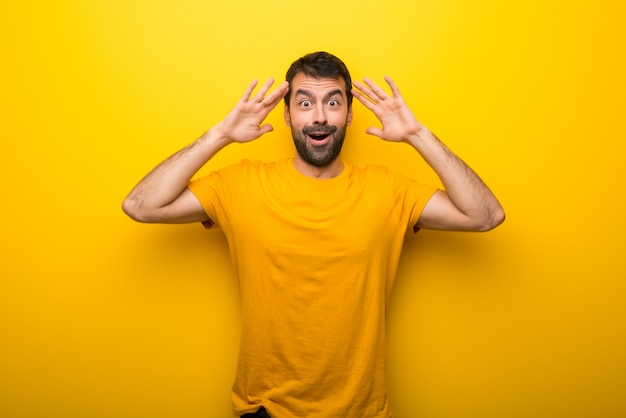 Man on isolated vibrant yellow color with surprise and shocked facial expression