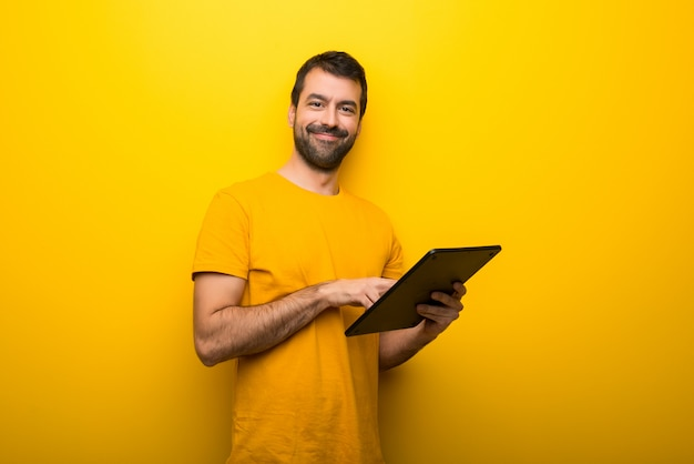 Man on isolated vibrant yellow color with a tablet